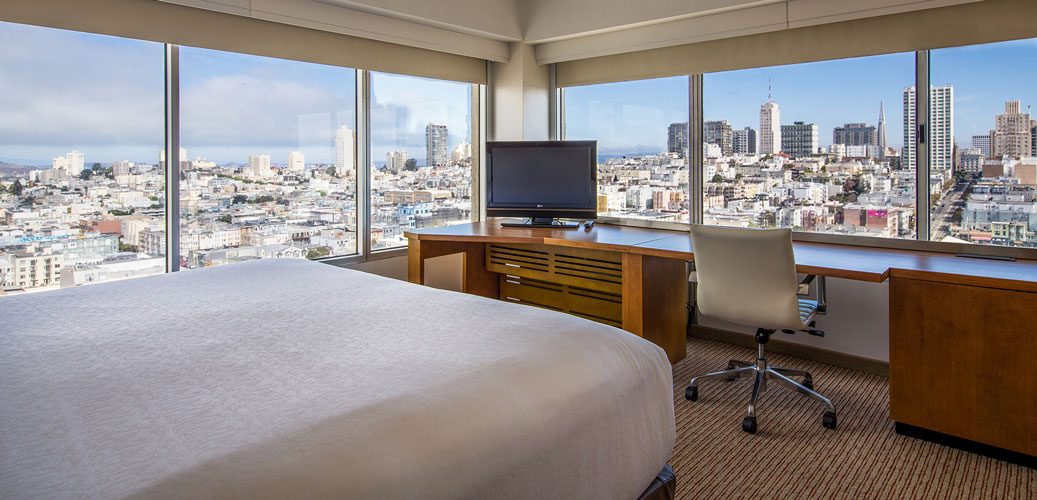 our corner king room showing king size bed and wrap-around windows for a view of Nob Hill on two sides
