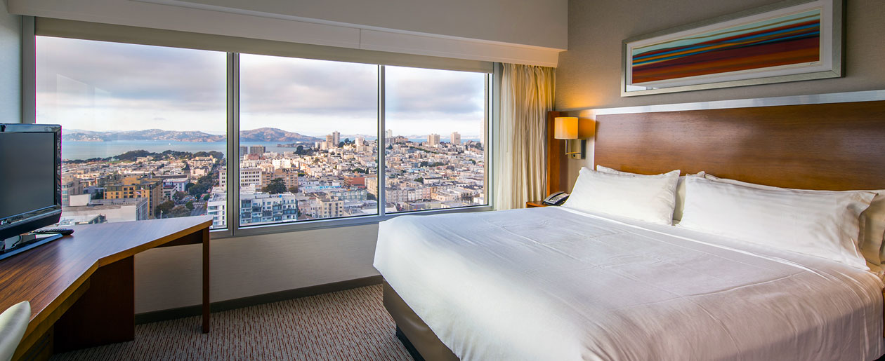 image of our guest rooms showing a king size bed, work desk and chair, and view of the skyline out the windows