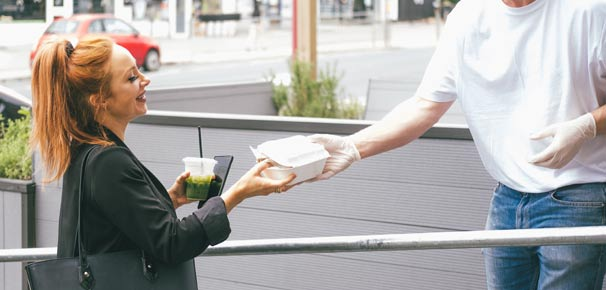 woman taking a to-go food box from a food server outside.
