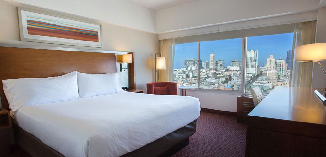 our grand view room showing one king bed and windows looking out to Nob Hill
