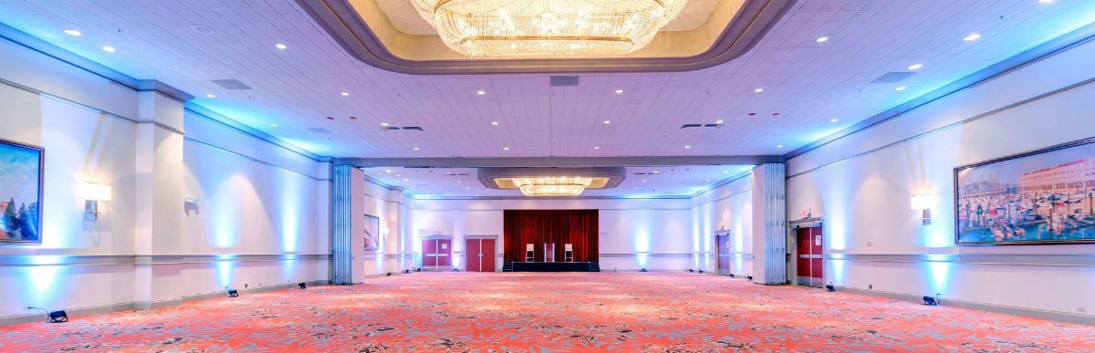 panoramic image of our ballroom empty with highlight lights on and stage showing