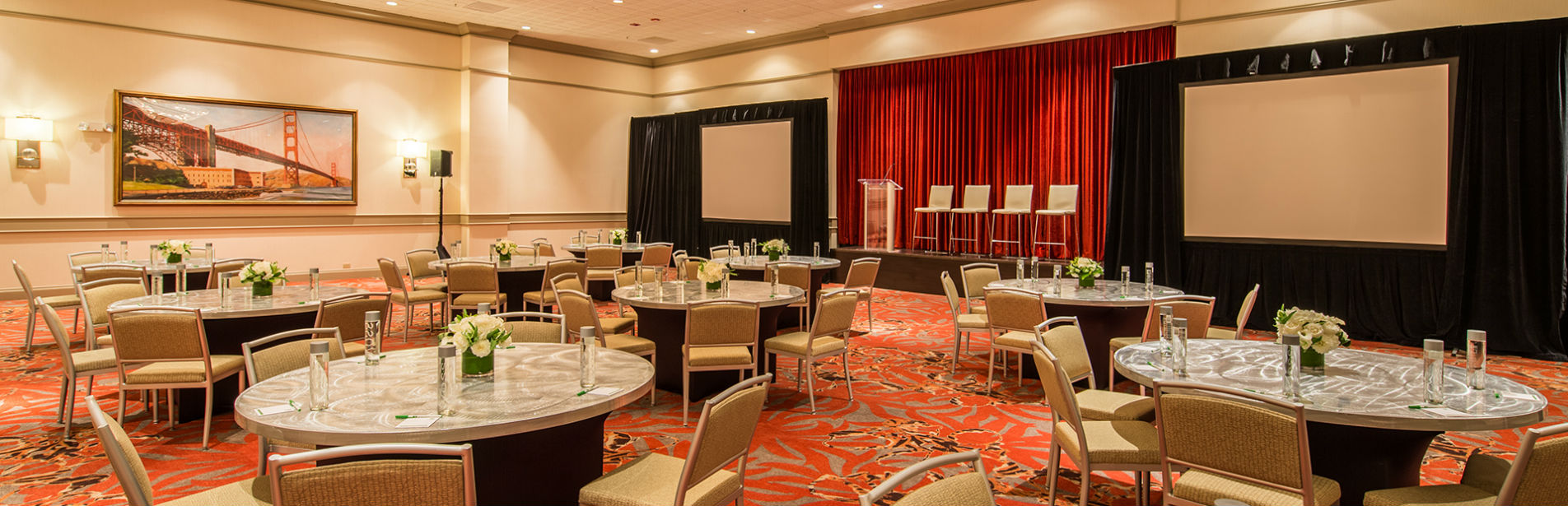 image of our ballroom set in banquet table rounds of 5 with screens and stage