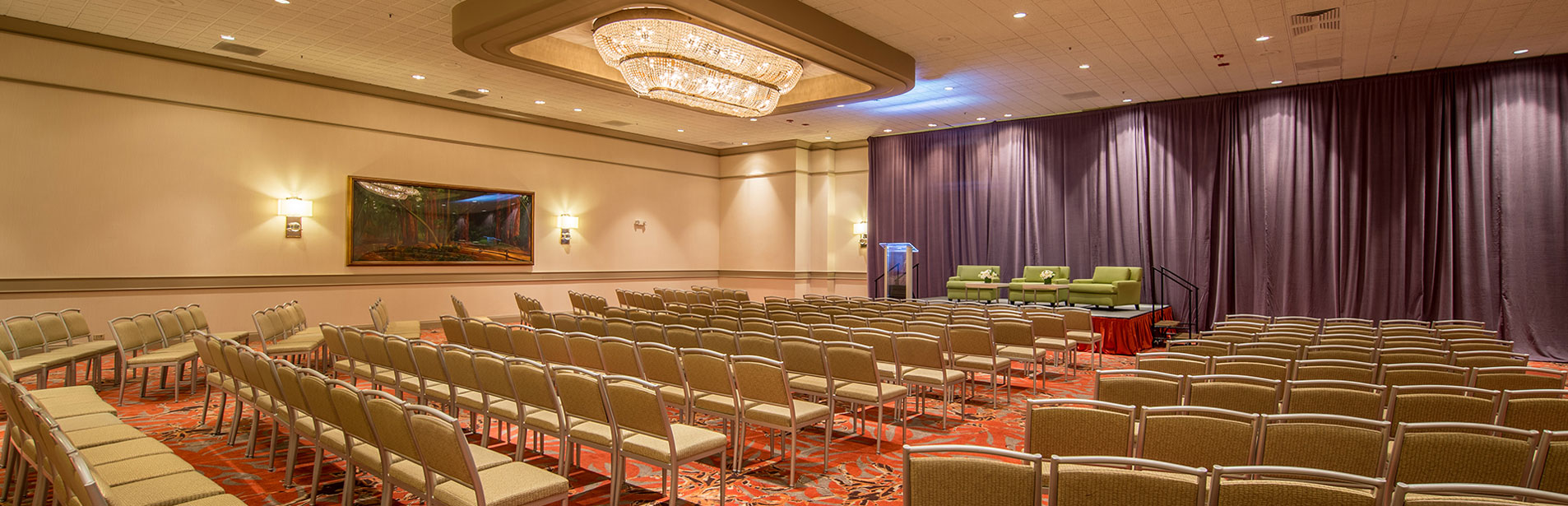 image of our ballroom set up theater style with stage and lectern at the front