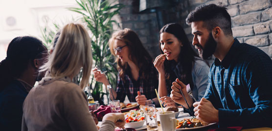 group of people sitting around a table enjoying a meal