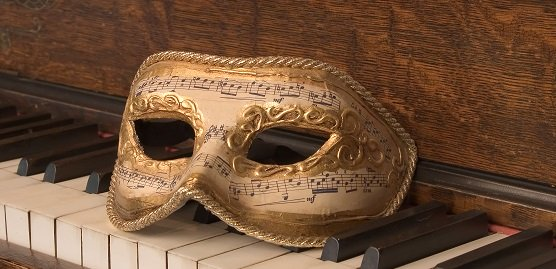 image of a mask sitting on a piano keyboard
